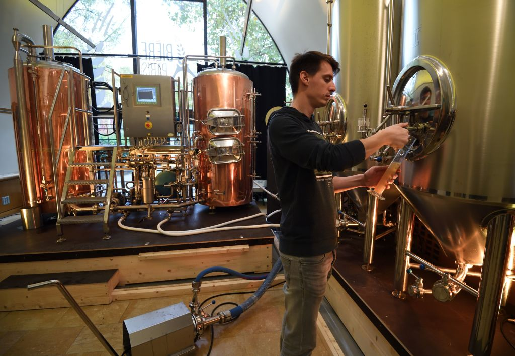 a brewer inspects a tank at a brewery in france, with copper stills behind him