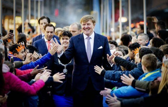 Dutch King Willem-Alexander (C) hands out high fives during the celebration of the 50th anniversary