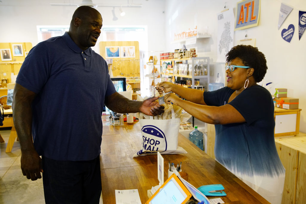 a man purchases goods at a small business from a woman behind a wooden counter