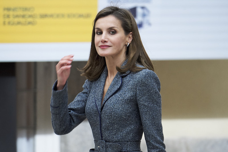 Queen Letizia of Spain smiles and holds up one hand
