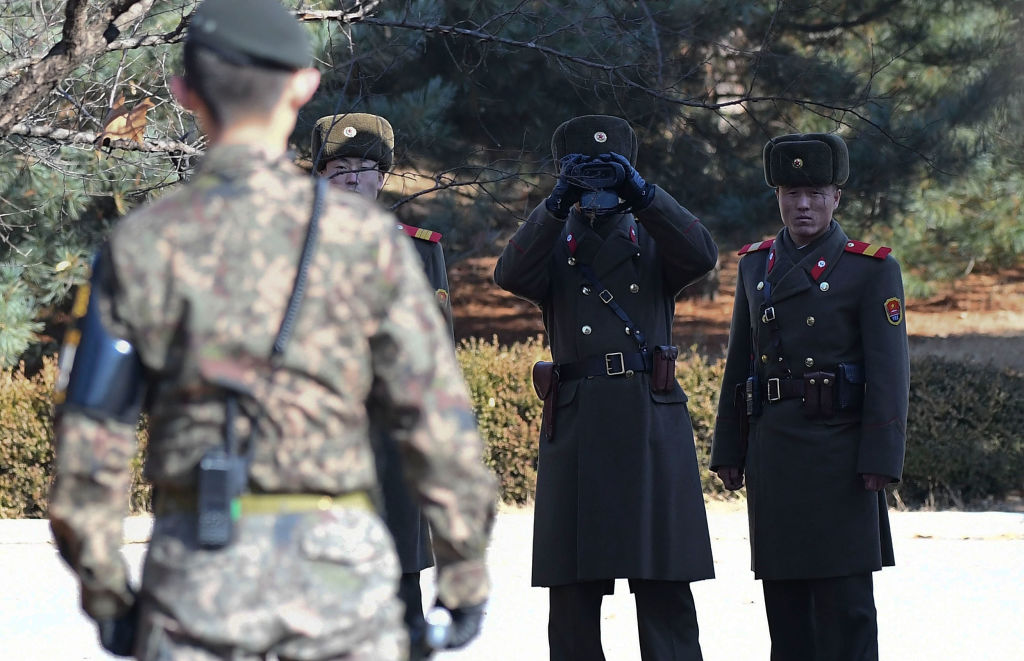 north korea military members in uniform, with a south korea military member in fatigues