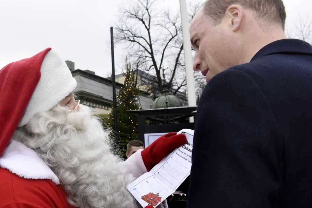 Prince William hands over a wish list by his son Prince George to a Santa Claus as he visits the Esplanade Park and the Manta's Market winter fair in Helsinki, Finland, on November 30, 2017.