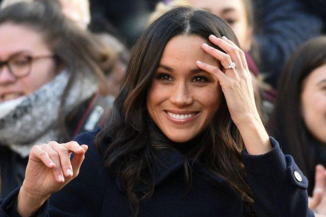 Meghan Markle smiling as she holds up her left hand.