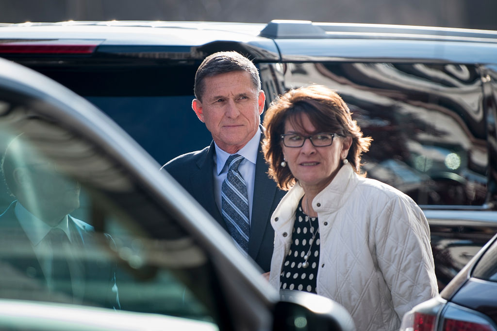 flynn in a dark suit and striped tie behind a car with a woman in white