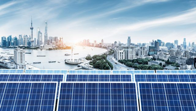 Solar panels juxtaposed to a chinese city landscape.