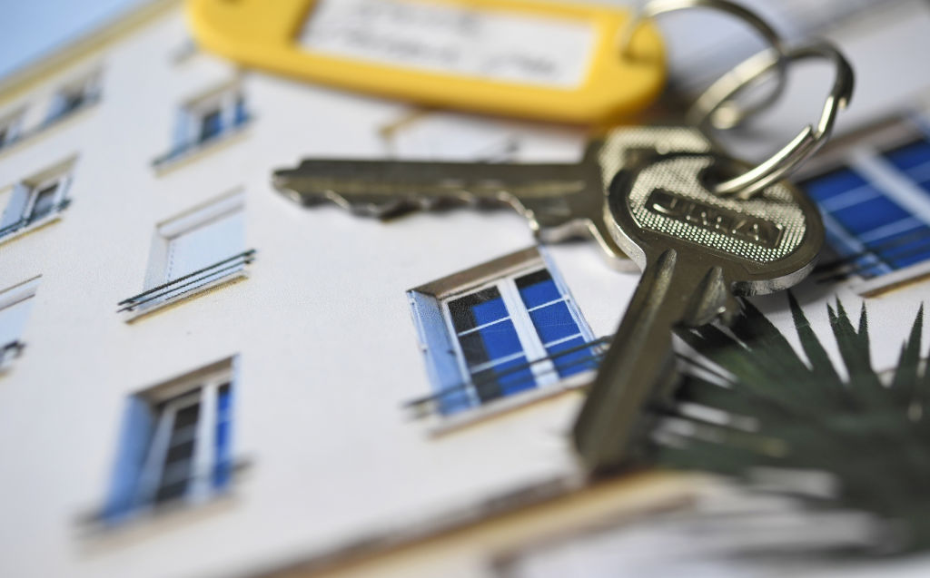 a pair of keys rests on a photo of a house