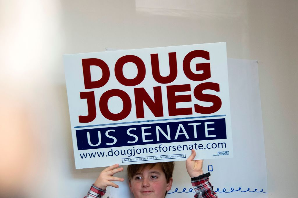 a young boy in plaid holds up a doug jones sign