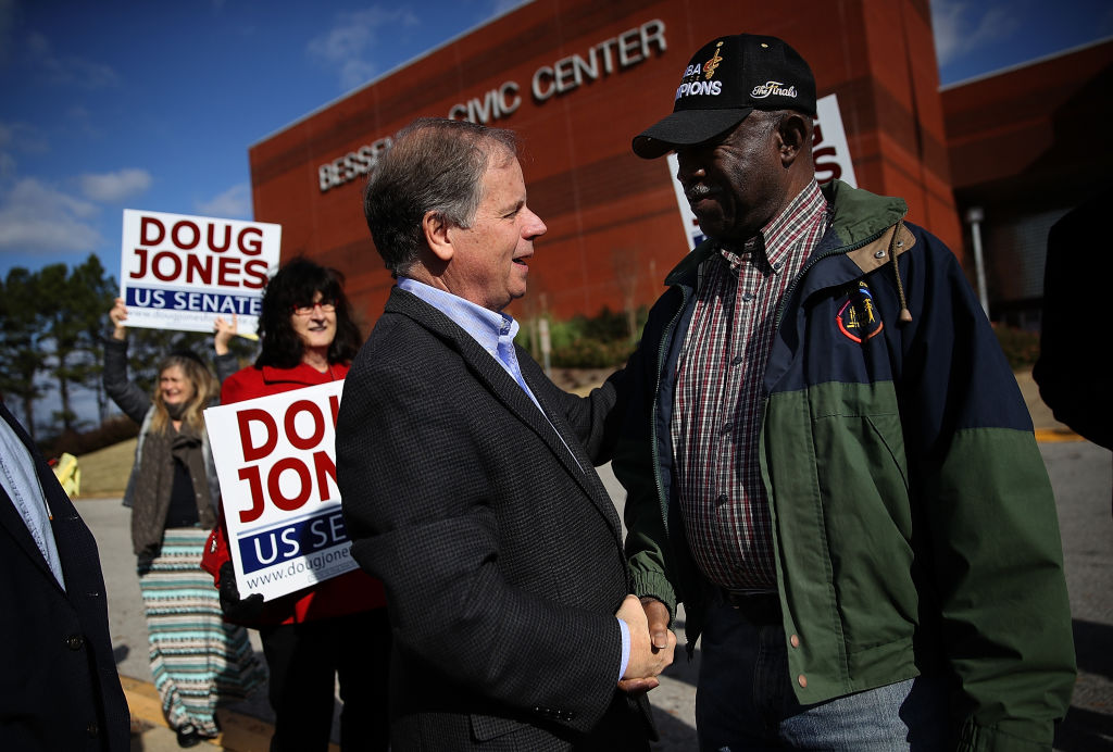 doug jones shakes hands with a voter outside a polling center