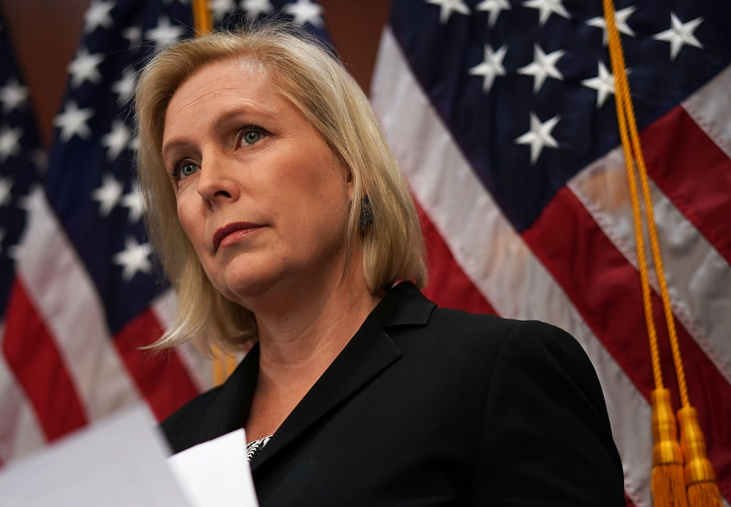 kirsten gillibrand in a dark suit against a flag