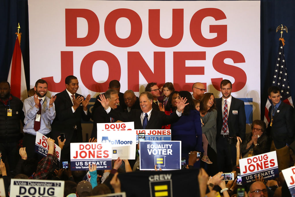 doug jones onstage with supporters on election night