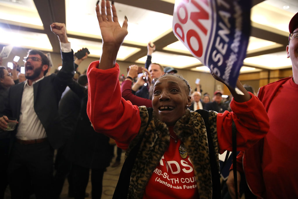 a woman in a red sweatshirt celebrates as election results come in