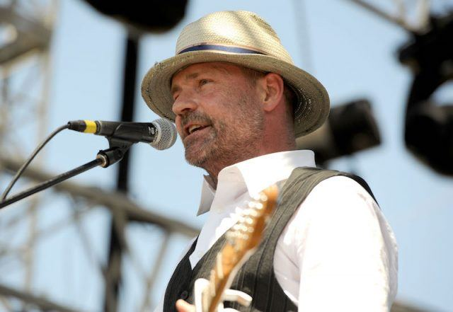 Gord Downie performs while holding a guitar.