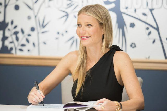 Gwenyth Paltrow signs a book and smiles.