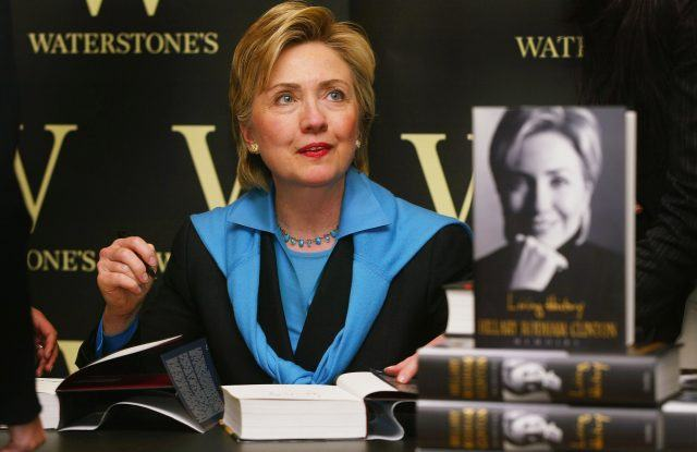 Hillary Clinton signing books while sitting and greeting fans.