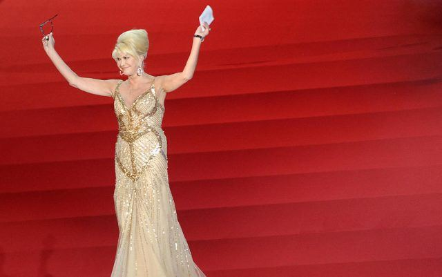 Ivana Trump wearing a gold gown while standing on red steps.