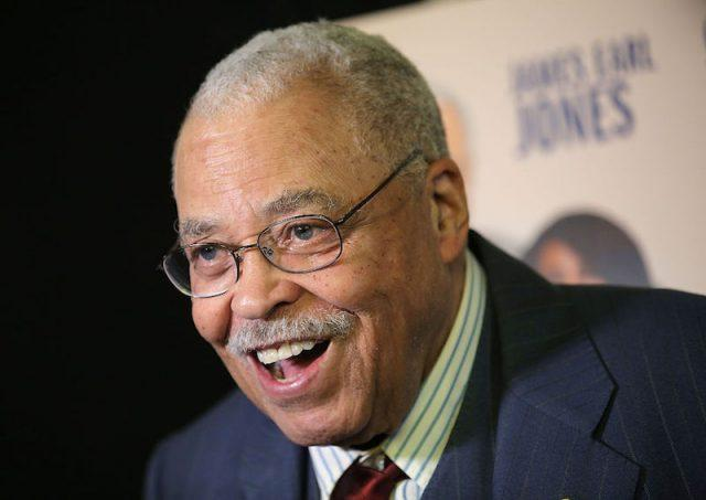 James Earl Jones smiling while wearing a suit and glasses