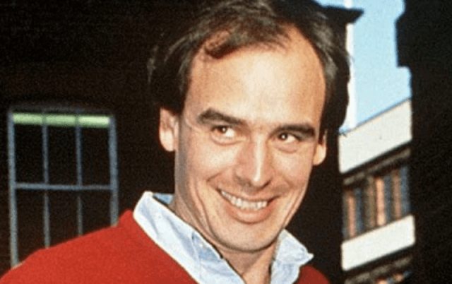 James Gilbey smiles while wearing a red sweater.