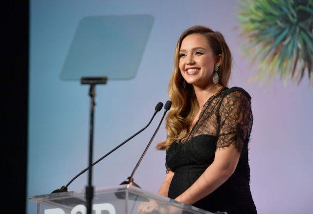 Jessica Alba smiles brightly while standing in front of a podium.
