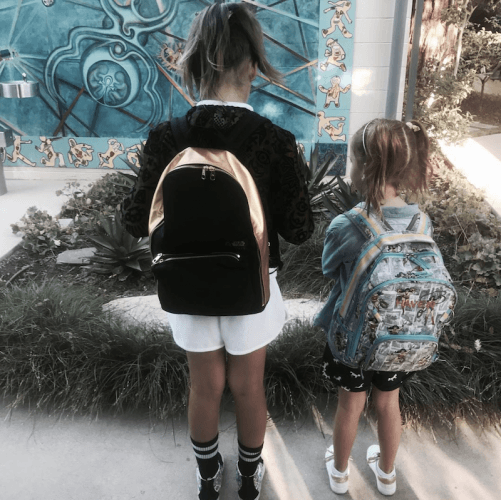 Jessica Alba's daughters stand wearing backpacks.