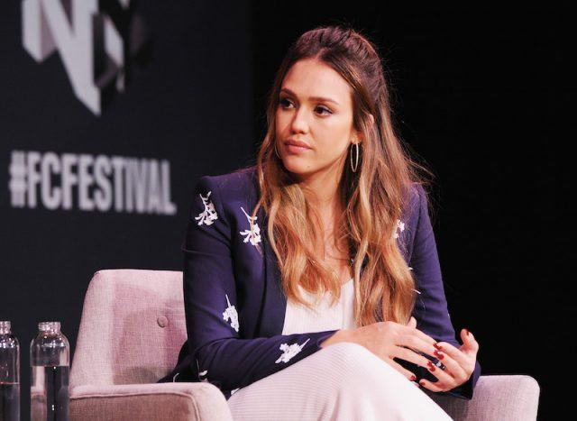 Jessica Alba sitting on a pink chair during an interview.