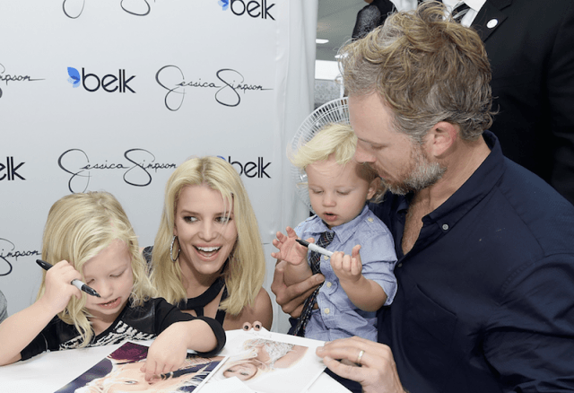 Jessica Simpson and Eric Johnson signing autographs with their children.