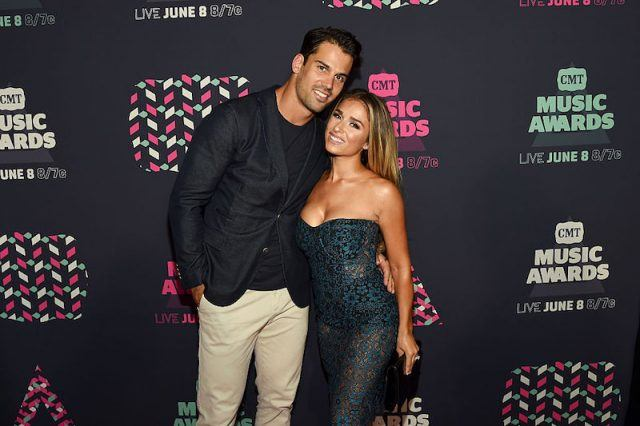 Eric Decker and Jessie James Decker smiling and hugging on a red carpet.