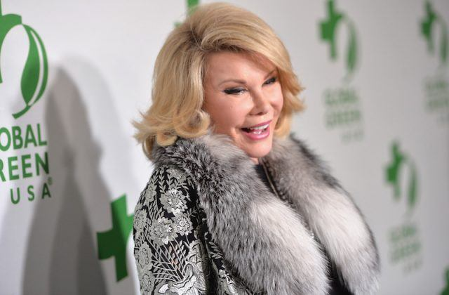 Joan Rivers smiles while wearing a fur jacket at an event.