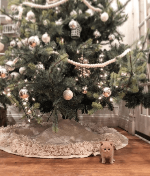 A silver and green Christmas tree with a tiny kitten