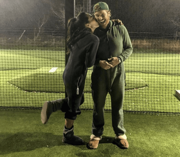 Joanna kisses Chip's cheek as they wear onesies on a field.