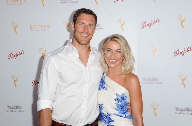 Julianne Hough and Brooks Laich smiling and holding each other as they pose for photographers.