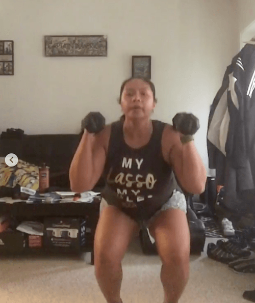 A woman doing jumping jack presses.
