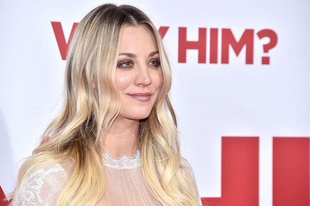 Kaley Cuoco smiles and poses on a red carpet wearing a white lace dress.
