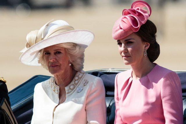 Camilla and Kate stand in front of a car.
