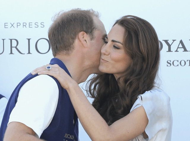 Prince William kisses Kate Middleton on the cheek.