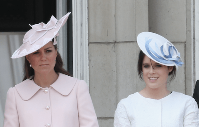 Princess Eugenia stands next to Kate Middleton on a balcony.