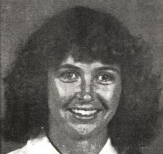 Kelly Dove smiling in a black and white photograph.