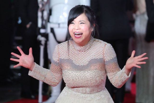 Kelly Marie Tran smiling while wearing a pearl and lace dress.