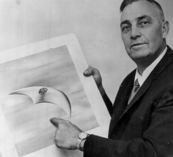 Kenneth Arnold pointing at a photo of a UFO.