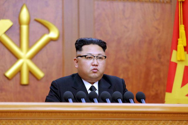 Kim Jong Un sits at a table with a set of microphones in front of him.