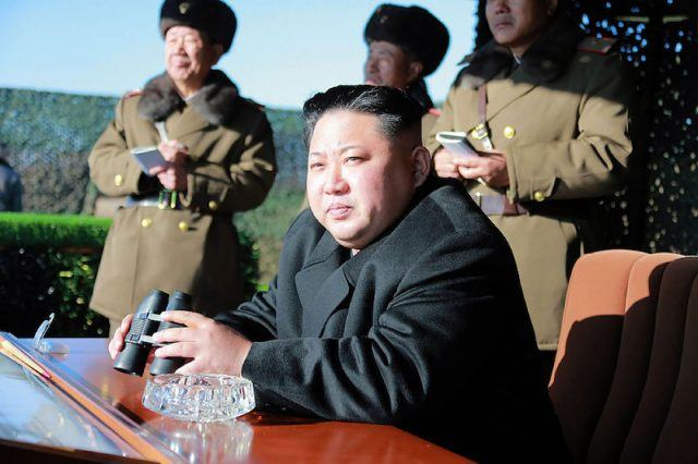 Kim Jong Un sits at a brown desk with a pair of binoculars.