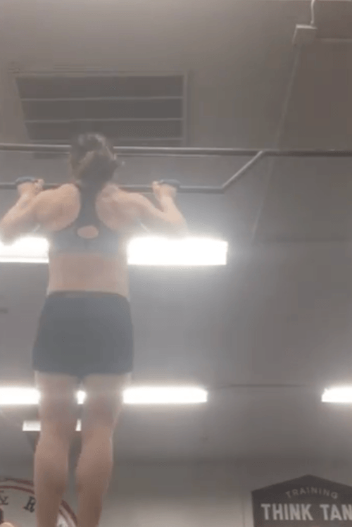 A woman doing a kipping pull-up.