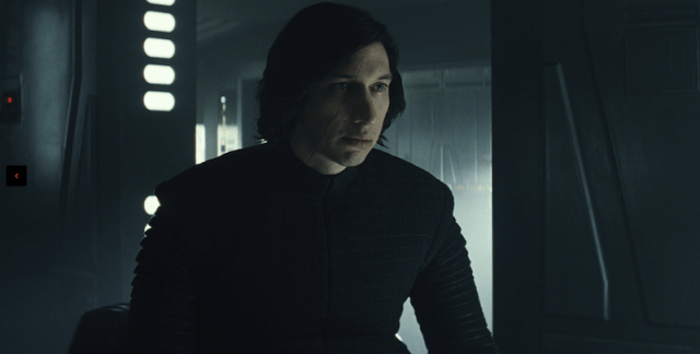 Kylo Ren sits inside a room while wearing black clothes.