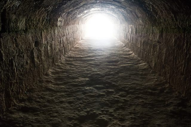 A bright light seen at the end of a brown tunnel.