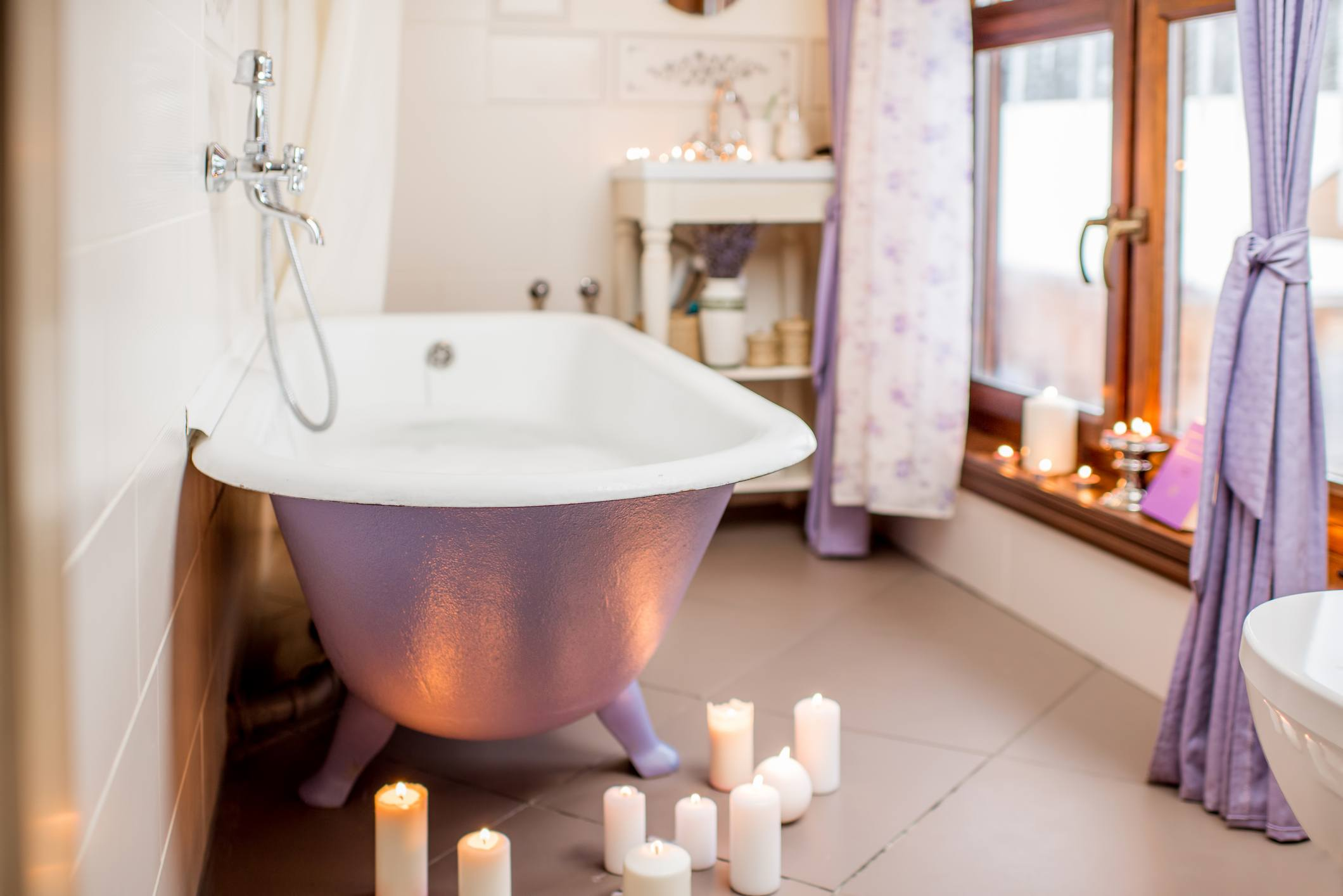 Bathroom interior with retro violet bath decorated with candles
