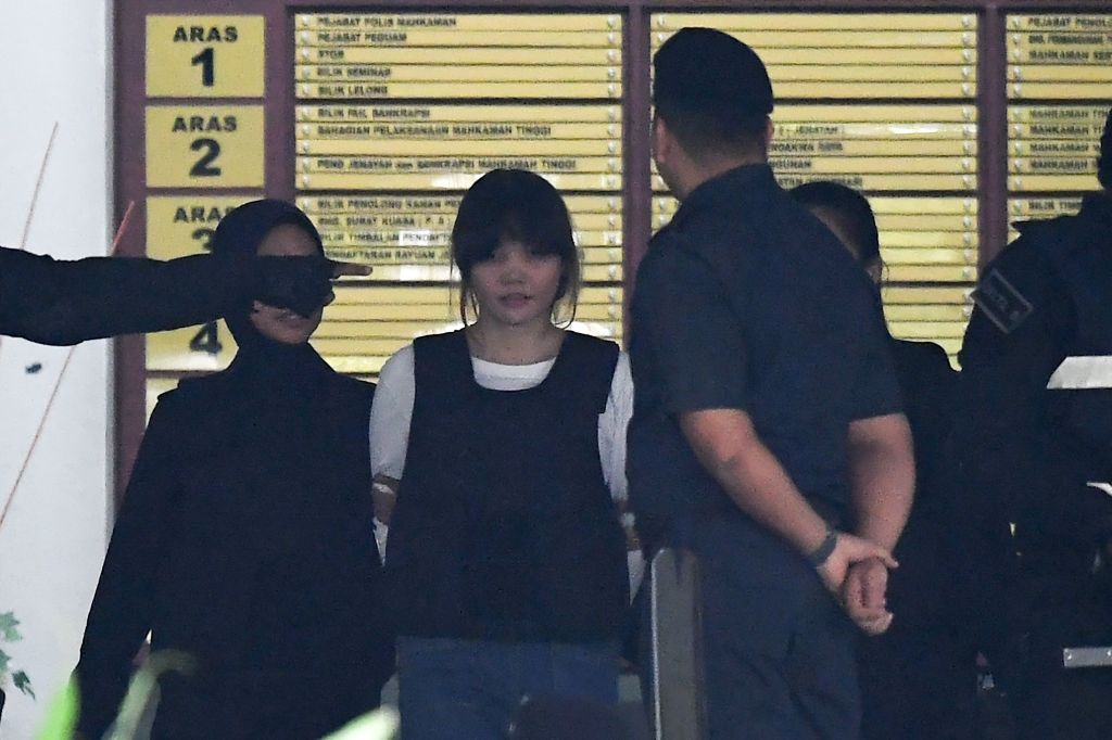 Royal Malaysian Police escort Vietnamese defendant Doan Thi Huong (2nd L) after her trial at the Shah Alam High Court in Shah Alam