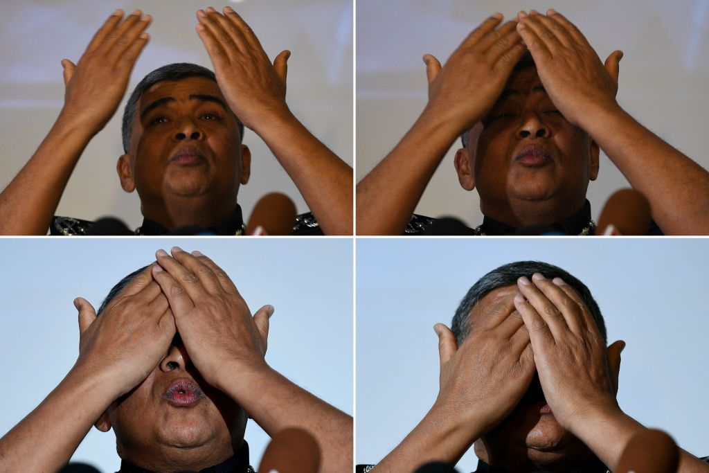 This combo of photographers taken on February 22, 2017 shows Royal Malaysian Police chief Khalid Abu Bakar demonstrating the actions of one of the women accused of being involved in the assassination of Kim Jong-Nam