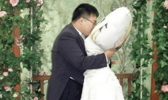 A man kissing his body pillow while it is dressed in a wedding dress.
