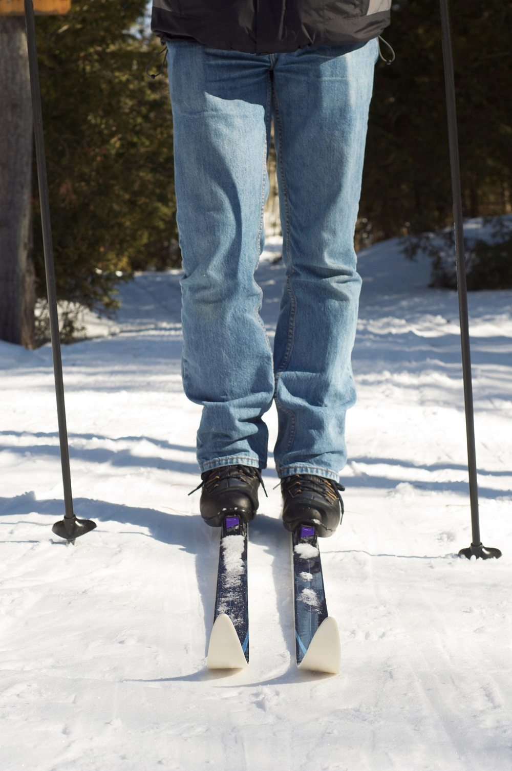 A man stands with his cross country skis