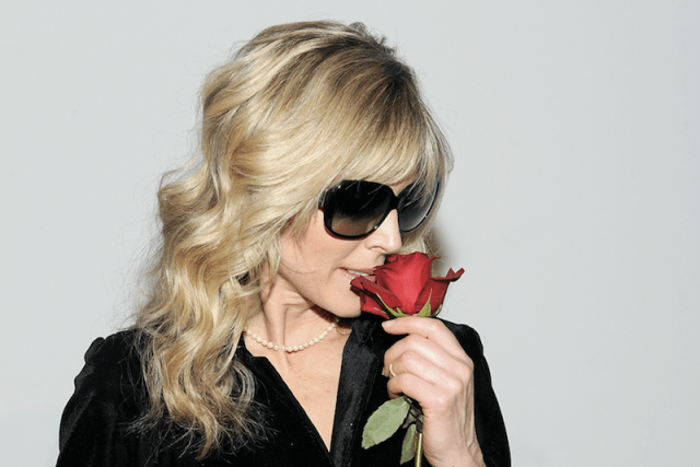 Marla Maples smelling a red rose.