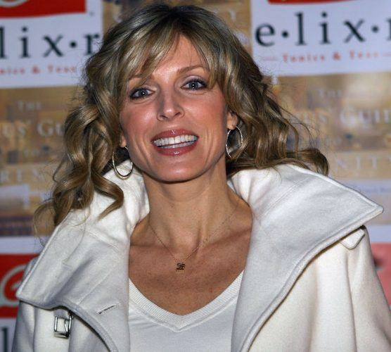 Marla Maples smiling in a white jacket.